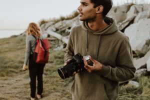 man in gray hoodie holding black dslr camera