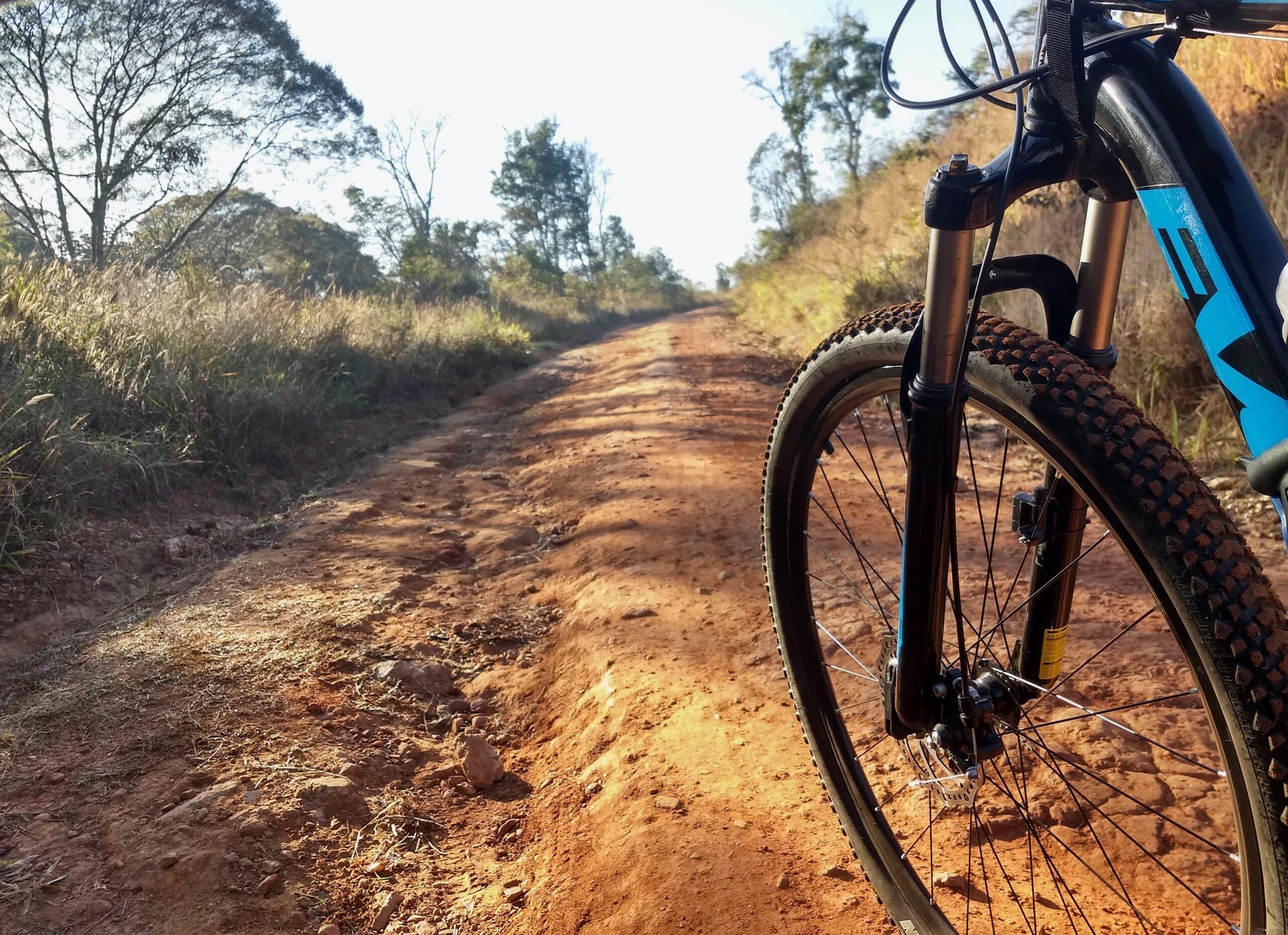 black mountain bike on brown dirt road during daytime