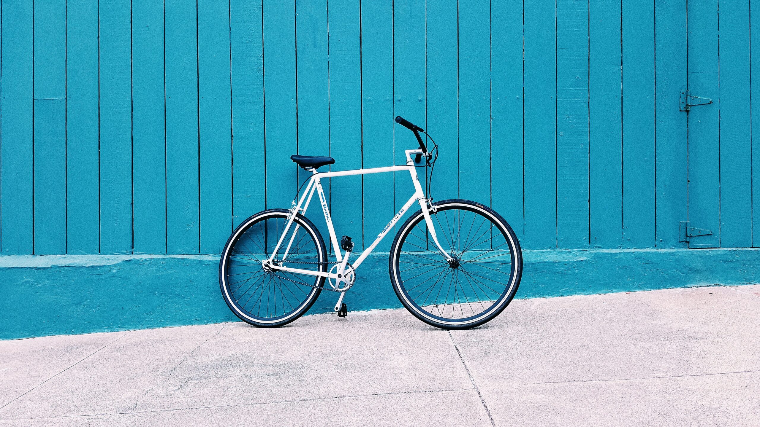 white road bike leaning on teal wooden wall during daytime